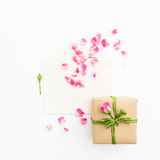 som bakgrund är kan vykortet använda valentiner Kronblad av rosor och pappers- kort för tappning, gåvaask på vit bakgrund Lekmann Arkivfoton