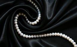 som bakgrund pryder med pärlor black silk white Arkivfoto