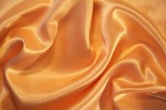 som bakgrund smooth eleganta guld- silk Arkivfoton