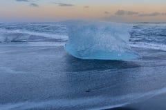 Is som bryter på den svarta sandstranden med solnedgånghimmelbakgrund Arkivbilder