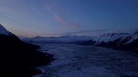 Is som flödar förbi berg i Alaska arkivfilmer