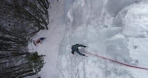 Is som klättrar den djupfrysta vattenfallet arkivfilmer