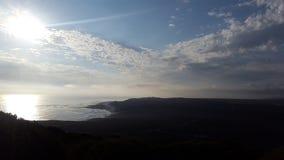 Som solen går ner och de ljusa strålarna framåt över havet Arkivfoto