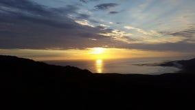 Som solen går ner och de ljusa strålarna framåt över havet Arkivbilder