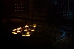 Som tändes upp stearinljus, stod vid böner i mörkret av ett kyrkligt rum på Notre Dame Cathedral, Paris Royaltyfria Foton