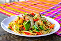 Som Tam Seafood Spicy Papaya Salad. With salted crab, on wooden table Thai food stock photo