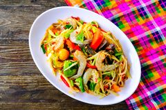 Som Tam Seafood Spicy Papaya Salad. With salted crab, on wooden table Thai food royalty free stock image
