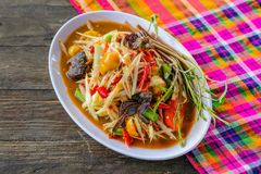 Som Tam Spicy Papaya Salad with salted crab, on wooden table. Thai food stock photos