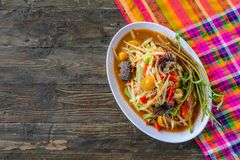 Som Tam Spicy Papaya Salad with salted crab, on wooden table. Thai food stock photo