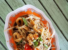 SOM-TAM, Thai delicious raw papaya salad with unique taste hot and spicy. This dish with crispy fried pork shrimp and topped up with green fresh tamarind seeds Royalty Free Stock Photos
