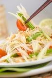 Som Tam Thai. Thai Green Papaya Salad with peanuts been picked up with chopsticks Royalty Free Stock Photos