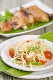 Som Tam Thai. Thai Green Papaya Salad with peanuts. Roast chicken in the background Royalty Free Stock Photo