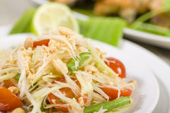 Som Tam Thai. Thai Green Papaya Salad with peanuts. Roast chicken in the background Royalty Free Stock Photography