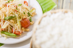 Som Tam Thai. Thai Green Papaya Salad with peanuts. Sticky rice out of focus in foreground Royalty Free Stock Photos