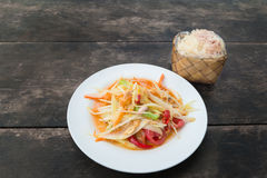 Som tam thai or Green papaya salad with sticky rice in bamboo co. Ntainer on wooden table at restaurant Royalty Free Stock Image