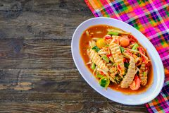 Som Tam Vietnamese Pork Sausage Spicy Papaya Salad. With salted crab, on wooden table Thai food stock photos