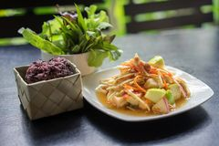 Som Tum Fruit Salad or Sour Spicy Thai fruit salad with Black Glutinous Rice in basket, Popular Thai-Eastern fusion food stock image