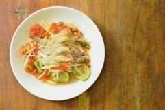 Som tum Thai spicy green papaya topping raw shrimp salad on plate. Som tum Thai spicy green papaya topping raw shrimp salad on white plate stock photography