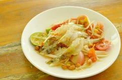 Som tum Thai spicy green papaya topping raw shrimp salad on plate. Som tum Thai spicy green papaya topping raw shrimp salad on white plate royalty free stock photo