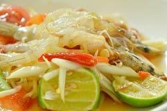 Som tum Thai spicy green papaya topping raw shrimp salad on plate. Som tum Thai spicy green papaya topping raw shrimp salad on white plate stock images