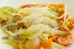 Som tum Thai spicy green papaya topping raw shrimp salad on plate. Som tum Thai spicy green papaya topping raw shrimp salad on white plate royalty free stock image