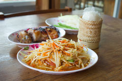 Som tum Thai. With sticky rice and grilled chicken on wooden table Stock Photography