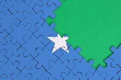 Somalia flag is depicted on a completed jigsaw puzzle with free green copy space on the right side.  royalty free illustration