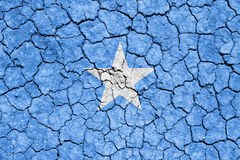 Somalia. The image of the flag of Federal Republic of Somalia on the cracked dry ground Royalty Free Stock Photography