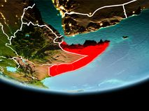 Somalia in red in the evening. Country of Somalia in red on planet Earth in the evening with visible border lines and city lights. 3D illustration. Elements of stock photos