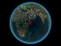 Somalia on planet Earth from space at night. Somalia in red with visible country borders and city lights from space at night. 3D illustration. Elements of this royalty free stock photo