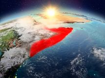 Somalia from space in sunrise. Satellite view of Somalia highlighted in red on planet Earth with clouds during sunrise. 3D illustration. Elements of this image royalty free stock photos
