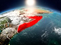 Somalia in sunrise from orbit. Sunrise above Somalia highlighted in red on model of planet Earth in space with visible country borders. 3D illustration. Elements royalty free stock images