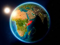 Somalia with sunset from space. Sunset above Somalia highlighted in red on planet Earth with visible country borders. 3D illustration. Elements of this image royalty free stock photo