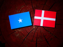 Somalian flag with Danish flag on a tree stump isolated. Somalian flag with Danish flag on a tree stump stock photo