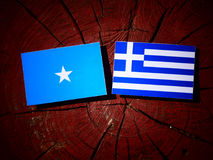 Somalian flag with Greek flag on a tree stump isolated. Somalian flag with Greek flag on a tree stump Royalty Free Stock Photos