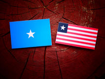 Somalian flag with Liberian flag on a tree stump isolated. Somalian flag with Liberian flag on a tree stump Royalty Free Stock Photos