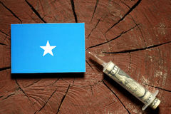 Somalian flag on a stump with syringe injecting money. In flag Royalty Free Stock Image