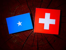 Somalian flag with Swiss flag on a tree stump. Somalian flag with Swiss flag on a tree stump Royalty Free Stock Images