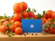 Somalian flaga na drewnianym panelu z pomidorami odizolowywającymi na whit obraz stock