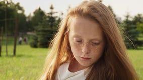 Somber gezicht van droevig gembermeisje met sproeten met verminderde ogen stock footage