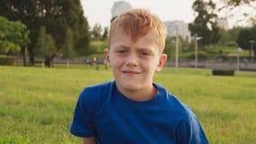 Somber gezicht van droevige roodharig weinig jongen met sproeten, zonnige de zomerdag in park stock videobeelden