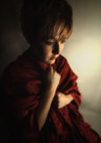Somber girl. Young woman in dramatic lighting trying to keep warm Stock Image
