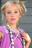 Somber Girl Playing Dress Up. Cute serious somber little girl blond hair playing dress up with jewelry and make up. Shallow depth of field Royalty Free Stock Images
