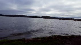 Somber meer onder donkere hemel in de zomerdag Bewolkte hemel over de duistere mening van het oever van het meerlandschap stock videobeelden