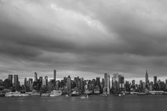 Somber Storm Clouds Over New York City. Somber and ominous are the thick, dark, clouds passing over the metropolis of New York Citys many towering buildings on royalty free stock photo