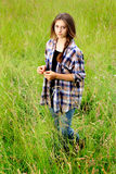 Somber Teen in Field. A pretty young teenage girl with long brown braided hair standing in a field of tall grass wearing a plaid shirt with a serious facial Stock Photography