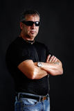 Somber tough guy. With tatoos and black sunglasses, arms crossed, looking at camera, studio shot over black Stock Photos