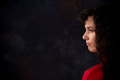 Somber Woman. Serious and somber looking woman against a dark background. Copy space on left Stock Image