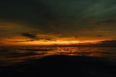 Sombere zonsondergang in avondoverzees Mooie zonsondergang in bewolkte hemel op oceaan Stock Foto