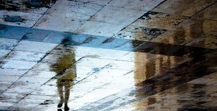 Sombra borrosa de la reflexión de una mujer en el pavimento mojado Fotografía de archivo libre de regalías